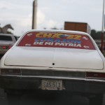 A car is seen with a campaign sign of Venezuela President Hugo Chavez in his hometown city and state of Barinas