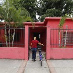 A woman arrives at an United Socialist Party office, which is located in the former house of Venezuela President Hugo Chavez's childhood town of Sabaneta