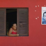 A woman looks out of a window in Venezuela President Hugo Chavez's childhood village of Los Rastrojos
