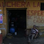 A man is seen in his mechanical garage next to a campaign poster of Venezuelan President Hugo Chavez in Barinas
