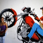 Girl stands next to graffiti depicting Venezuela's President Hugo Chavez on a motorcycle in Caracas