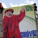 People hang a poster depicting Venezuelan President Hugo Chavez as a rap singer during a boxing tournament at a slum in Los Teques