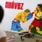 A woman looks at graffiti depicting Venezuela's President Hugo Chavez in the suburbs of Caracas
