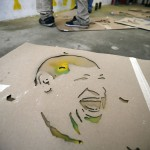 Stencil of the face of Venezuelan President Hugo Chavez lies on the floor as 'Communication Army' members paint in a suburb of Caracas