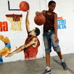 Boy plays basketball in front of a painting of President Hugo Chavez dunking a ball in Petare in the suburbs of Caracas
