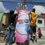 Boys hang up a banner depicting Venenezuelan President Hugo Chavez during a boxing tournament at a slum in Los Teques