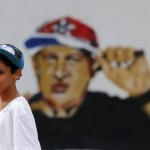 A boy plays in front of a graffiti depicting Venezuela's President Chavez as a rap singer in Petare, in the suburbs of Caracas