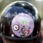 Motorcyclist wearing helmet with sticker depicting Venezuelan President Chavez watches boxing tournament at slum in Los Teques
