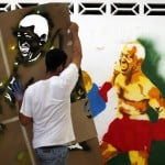Aldemaro from the 'Communication Army' paints graffiti depicting Venezuela's President Hugo Chavez as a boxer in a Caracas suburb