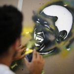 A member of the 'communication army' works on graffiti depicting Venezuela's President Chavez at the suburbs of Caracas