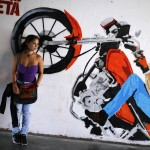 A girl stands next to graffiti depicting Venezuela's President Hugo Chavez on a motorcycle in Caracas