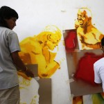 Members of the 'communication army' spraypaint graffiti depicting Venezuela's President Chavez in the suburbs of Caracas