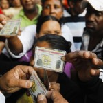 Venezuelans show their IDs as they line up to cast their votes during Presidential election in Caracas