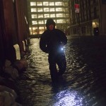 A security guard walks through a flooded street in the financial district of Manhattan