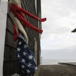 An American Flag windsock is wrapped around the side of a building as clean up begins from Hurricane Sandy in Scituate