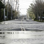A power line lies fallen across a road flooded by floodwaters pushed up by high tide and the storm surge from Hurricane Sandy in Westhampton Beach