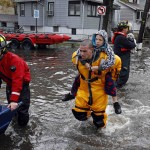 A rescue worker carries a boy on his back as emergency personnel rescue residents from flood waters brought on by Hurricane Sandy in Little Ferry