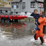 A rescue worker carries a young girl to safety from flood waters brought on by Hurricane Sandy in Little Ferry