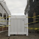 The missing pieces of a fence are wrapped in caution tape as the region begins to clean up from Hurricane Sandy in Scituate