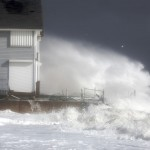 Waves crash against the shoreline during high tide in Milford, Connecticut