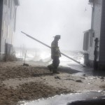 A firefighter is sprayed by waves while going door-to-door looking for stranded residents in Milford, Connecticut