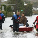 Members of the Patchogue Fire Department escort stranded residents from their homes on a boat in Patchogue, New York