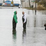 Two men in waders speak with another man in a vehicle about the state of their homes while surveying damage from Hurricane Sandy in Patchogue, New York