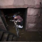 A woman removes a bicycle from a flooded basement on 14th street after the storms from last night's Hurricane Sandy in New York