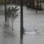 Floodwaters surround a car parked on a street in Hoboken, New Jersey