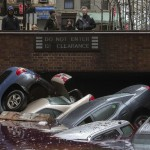 Residents stand over vehicles which were submerged in a parking structure in the financial district of Lower Manhattan, New York