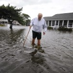 A man walks in ankle-deep water from his house in the aftermath of Hurricane Sandy in South Bethany Beach