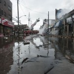 Firefighters work to extinguish a fire on a flooded street in the Rockaways section of New York