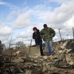 A man stands with Lucille Dwyer on among the wreckage of their homes devastated by fire and the effects of Hurricane Sandy in the Breezy Point section of the Queens borough of New York