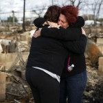 Neighbors Lucille Dwyer and Linda Strong embrace after looking through the wreckage of their homes devastated by fire and the effects of Hurricane Sandy in the Breezy Point section of the Queens borough of New York