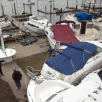 Men inspect damaged boats at the Varuna Boat Club in the Brighton Beach neighborhood of New York