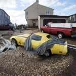 A Corvette and truck moved by the storm surge from Hurricane Sandy rest in a driveway in Lindenhurst, New York