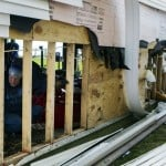 A man cleans up his garage from damage done to it by Hurricane Sandy in Lindenhurst, New York