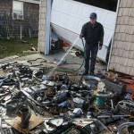 A man rinses motorcycle parts on his driveway after getting them from his home that was damaged by Hurricane Sandy in Lindenhurst, New York
