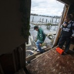 Joseph Messina and Donna McBride inspect damage done to their home by the storm surge of Hurricane Sandy in Lindenhurst, New York