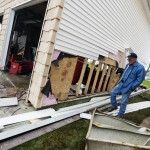 A man checks damage from storm surge and wind to his home in Lindenhurst, New York