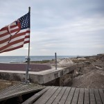 A torn United States flag flies above the destroyed infrastructure of the boardwalk in the Rockaway Beach neighborhood of Queens, New York