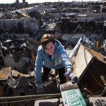 McLoughlin helps sort through the remains of her father's house, which burned to the ground during Hurricane Sandy, in the Breezy Point neighborhood of Queens, New York