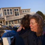 Evelyn Faherty hugs a friend while discussing the damage to her home in the Breezy Point neighborhood of Queens, New York