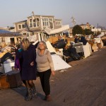 Two women survey the damage to waterfront properties in the Breezy Point neighborhood of Queens, New York