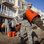 National Guard soldiers dump buckets of sand from Monir Islam's home after Hurricane Sandy hit in the Rockaway Park neighborhood of Queens, New York
