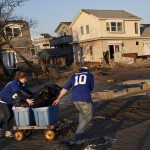 A man and woman use a wagon to wheel out belongings to their car after Hurricane Sandy hit, in the Breezy Point neighborhood of Queens
