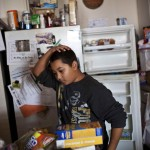 A boy glances at food donated to his family after Hurricane Sandy hit, in the Rockaway Park neighborhood of Queens in New York