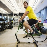 An employee demonstrates the use of an exercise cycle, that powers a blender making a fruit smoothie, inside the employee gym at the new Google office in Toronto