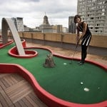 Google employee Andrea Janus demonstrates the use of the mini-putt green on the balcony at the new Google office in Toronto