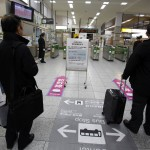 Men stand near a sign alerting passengers to a suspension in bullet train services in northeastern Japan due to an earthquake, at Nagano train station, central Japan